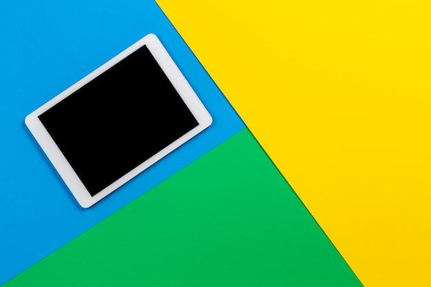 Digitales tablet auf hellblauem, grünem und gelbem hintergrund