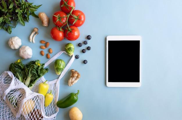 Digitales tablet mit öko-tasche und frischem gemüse. online-anwendung zum einkaufen von lebensmitteln und produkten für biobauern. lebensmittel- und kochrezept oder ernährungszählung.