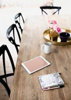 Digitales tablet und ein notizbuch mit marmorstruktur auf einem esstisch aus holz