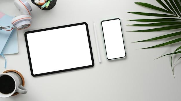 Digitales tablet und ein smartphone auf einem weißen schreibtisch