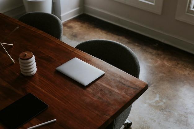 Digitales tablet und laptop auf einem holztisch in einem besprechungsraum