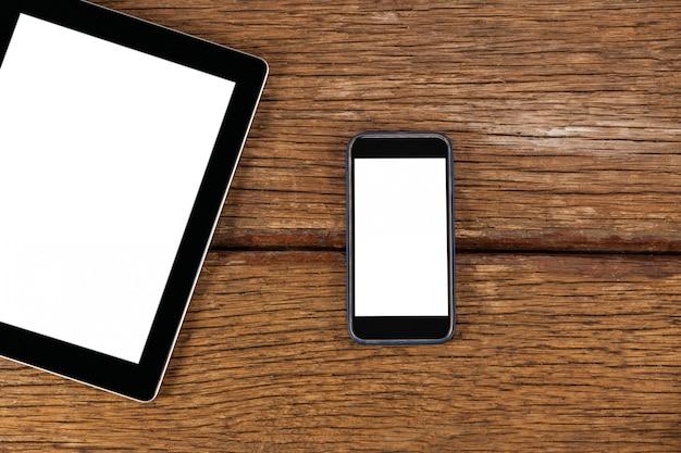 Digitales tablet und smartphone auf holzbrett