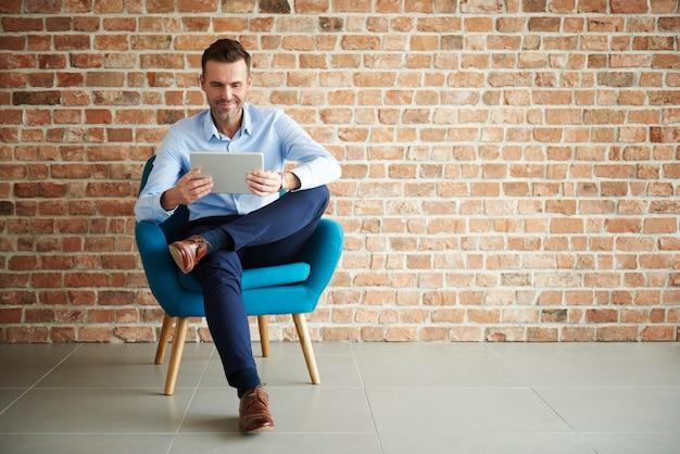 Digitales tablet von gutaussehenden mann verwendet
