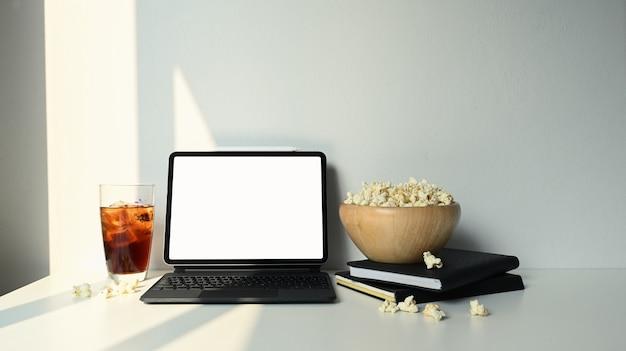 Digitales tablett mit leerem bildschirm und einer schüssel popcorn auf weißem schreibtisch.