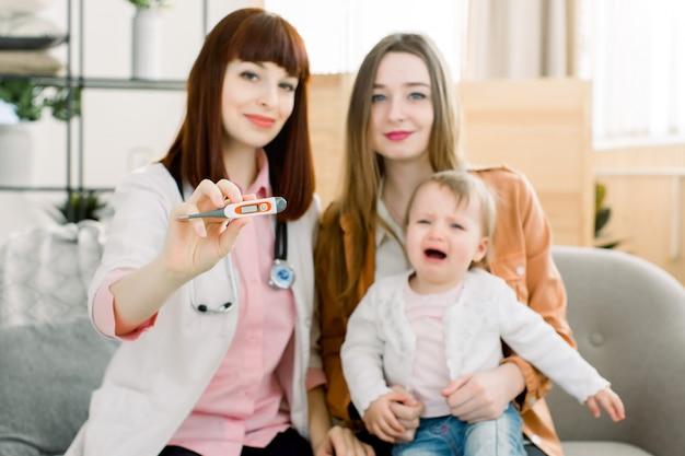 Digitales thermometer zur messung der hitzetemperatur eines kranken kindes. baby-fieber-konzept. doktor, mutter und ihr kleines mädchen weinen in der klinik