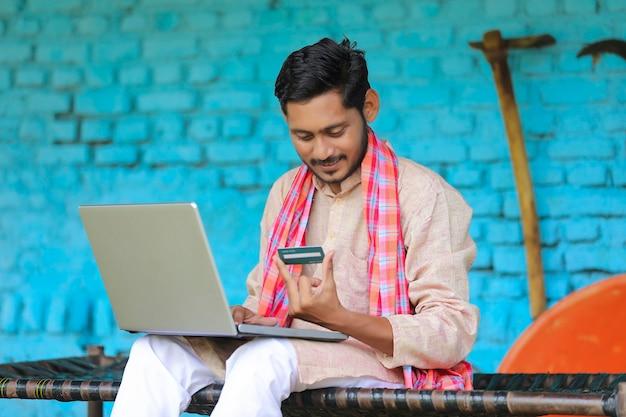 Digitales zahlungskonzept: indischer bauer mit laptop und karte zu hause
