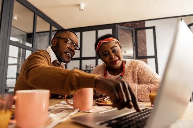Digitales zeitalter. freudiger afroamerikanischer mann, der einen knopf drücken möchte, während er mit seiner frau spricht