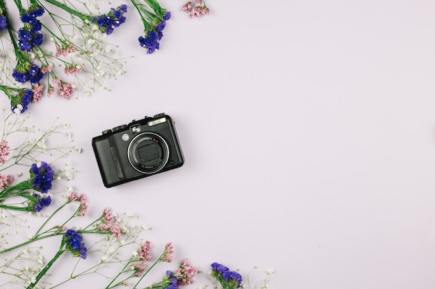 Digitalkamera mit blumendekoration auf weißem hintergrund