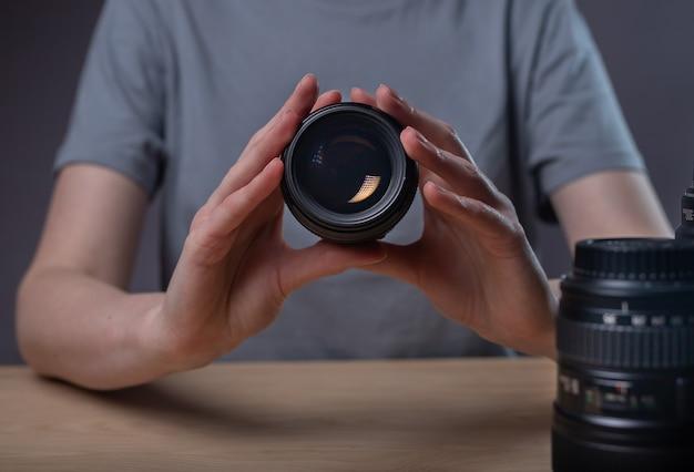 Digitalkamera-objektiv 85 mm in den händen einer fotografin über dem schreibtisch.