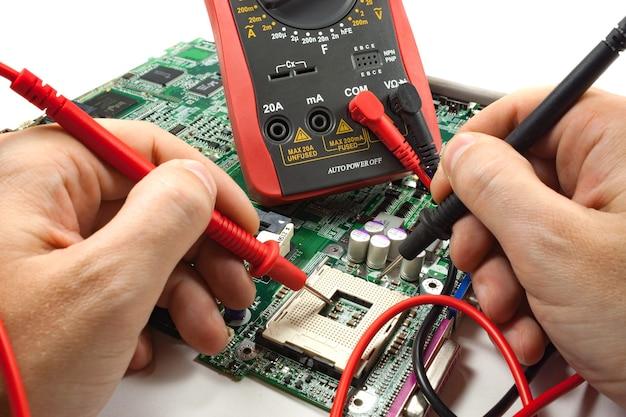 Digitalmultimeter mit sonde in den händen des meisters in einer werkstatt