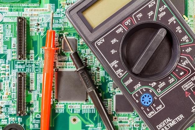 Digitalmultimeter und sonden auf einer grünen leiterplatten-nahaufnahme