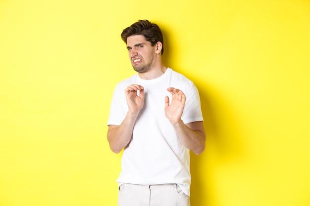 Digusted kerl weigert sich und verzieht das gesicht, schaut etwas mit abneigung an und steht über gelbem hintergrund. speicherplatz kopieren
