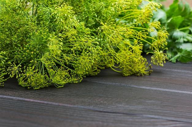 Dillzweige mit samen und petersilie. grüns als gewürz zum fermentieren von gemüse. hölzerner hintergrund. ansicht von oben. platz kopieren