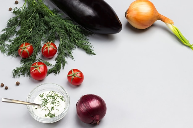 Dillzweige und kirschtomaten sauce in glasschüssel zwei zwiebeln auf dem tisch