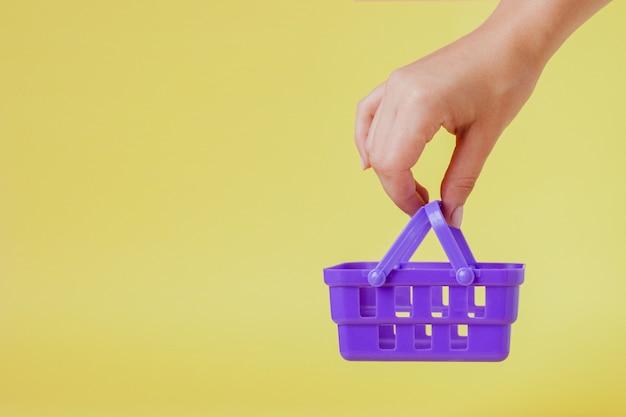 Dinge auf dem markt kaufen. frauenhand, die kleine kleine einkaufskorblaufkatze über tendenzgelb hält.