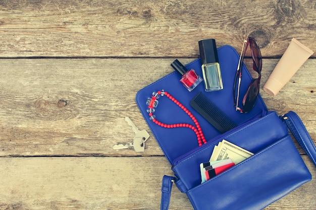 Dinge aus offener geldbörse. kosmetik, geld und damenaccessoires fielen aus der blauen handtasche. draufsicht. getöntes bild.