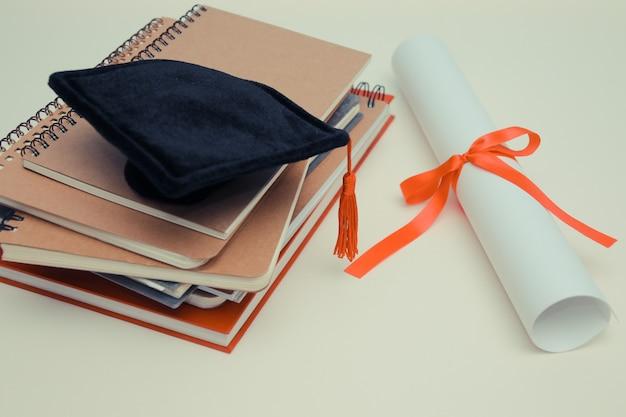 Diplom mit rotem band und schwarzer staffelungskappe auf holz