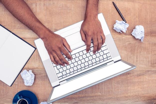 Direkt geschossen vom betonten geschäftsmann unter verwendung des laptops am schreibtisch im büro