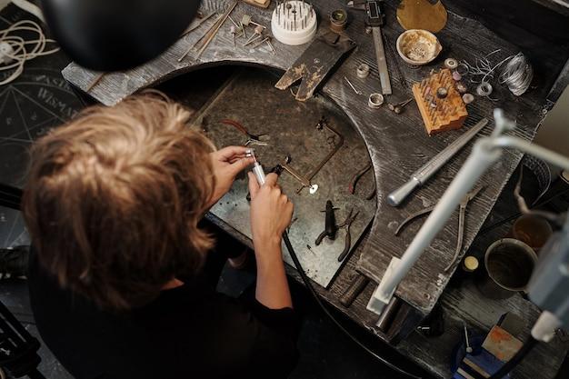Direkt über dem herstellungsjuwelier mit schleifmaschine während der herstellung von ringen in schmuckwerk...