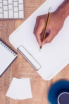 Direkt über dem schuss des geschäftsmannschreibens auf notizbuch durch computertastatur am schreibtisch im büro
