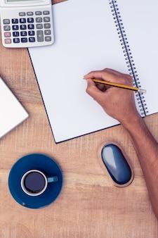 Direkt über dem schuss des geschäftsmannschreibens auf notizbuch durch kaffee am schreibtisch im büro