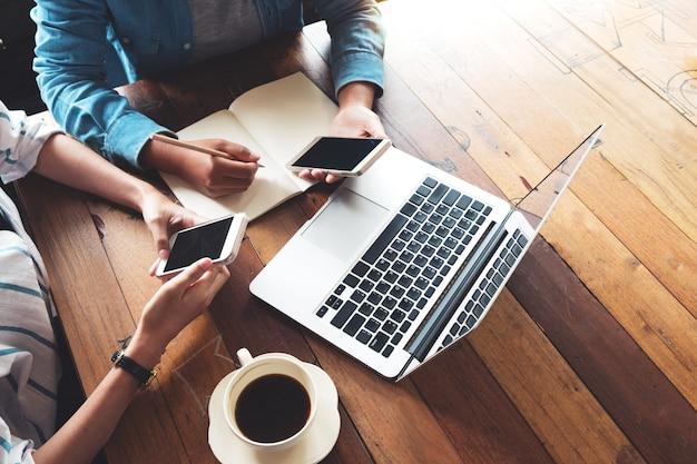 Direkt über geschäftsfrauen mit laptop und handy in der kaffeestube