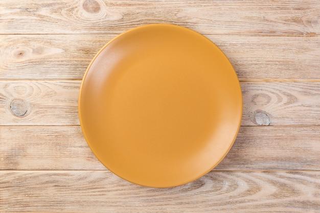 Direkt über leerem orange mattteller für abendessen auf orange hölzernem hintergrund