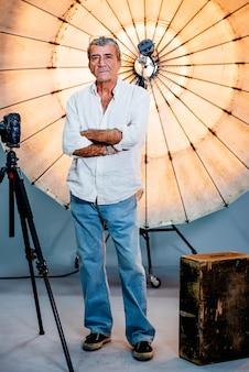 Direktor, der vor einem reflektierenden regenschirm in einem studio steht