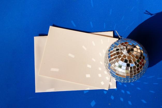 Disco bälle auf blauem hintergrund mit leerer papierkarte