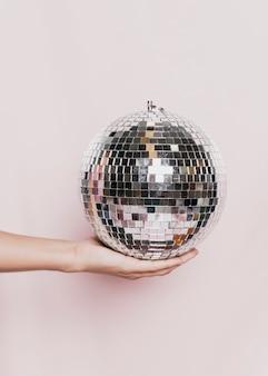 Discokugelhand gehalten an der party der neuen jahre