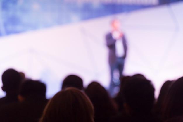 Disfocus des sprechers, der über die geschäftskonferenz spricht. publikum im konferenzsaal. veranstaltung für business und entrepreneurship.