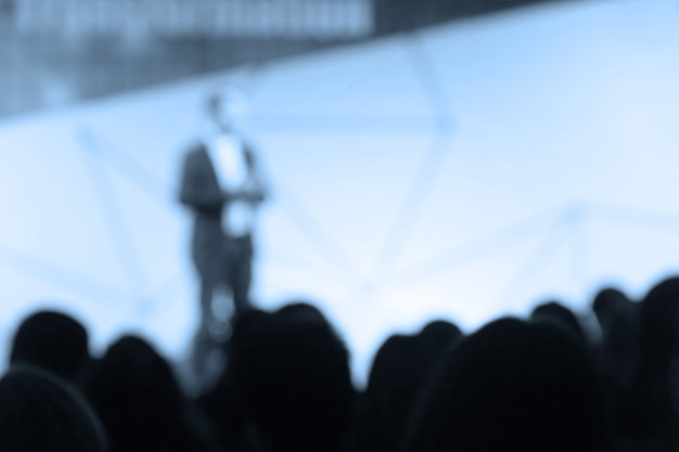 Disfocus des sprechers, der über die geschäftskonferenz spricht.