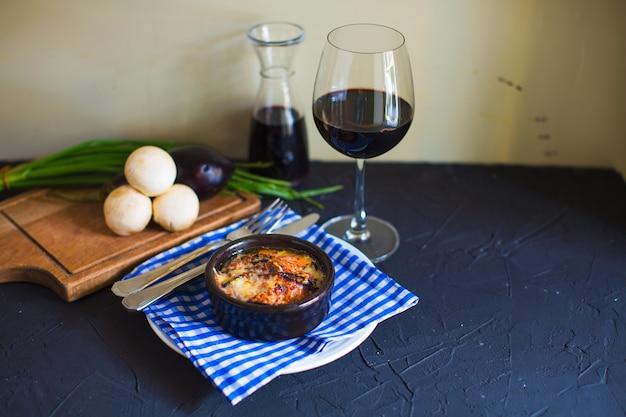 Dish mit geschmolzenem käse in kleinen töpferpfanne mit rotwein serviert