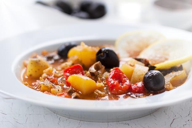 Dish von kartoffeln mit schwarzen oliven und tomaten