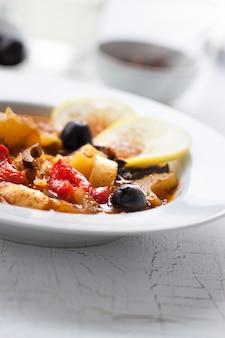 Dish von kartoffeln mit schwarzen oliven und zitronen