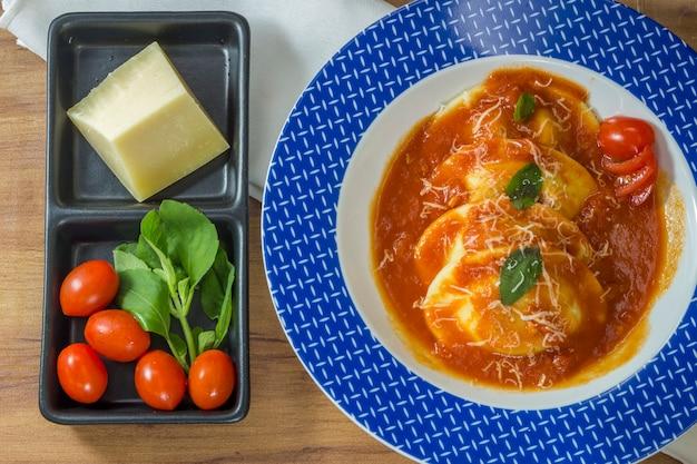 Dish von sorrentinos - pasta gefüllt - mit sauce und mit einigen basilikumblättern dekoriert.