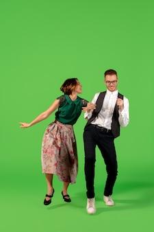 Disko. altmodische junge frau tanzen auf grünem studiohintergrund isoliert. künstlermode, bewegungs- und aktionskonzept, jugendkultur, moderückkehr. junger stilvoller mann und frau.