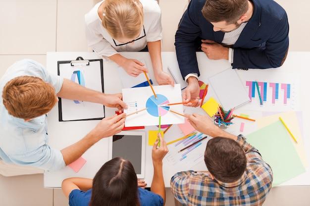 Diskussion über diagramm. draufsicht von geschäftsleuten, die beim sitzen am tisch auf diagramme zeigen