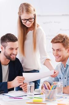 Diskussion über neues projekt. drei selbstbewusste geschäftsleute in eleganter freizeitkleidung diskutieren etwas, während sie sich das dokument gemeinsam ansehen