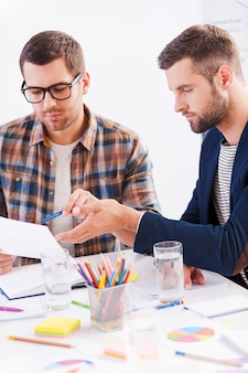 Diskussion über neues projekt. zwei selbstbewusste geschäftsleute in smarter freizeitkleidung sitzen zusammen am tisch und diskutieren etwas
