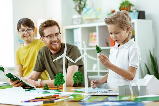 Diskussion über ökologie. neugieriger junger student, der ein plastikbeispiel eines baumes trägt und ihn aufmerksam inspiziert