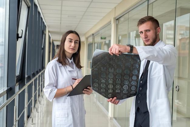 Diskussion zwischen 2 ärzten über die behandlung eines patienten, der sich eine gehirn-mrt ansieht. gesundheit