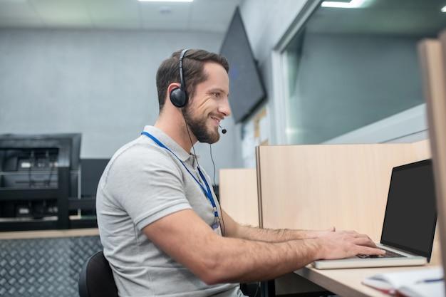 Dispatcher, informationen. attraktiver bärtiger junger mann im kopfhörer mit mikrofon, das am computer im büro arbeitet
