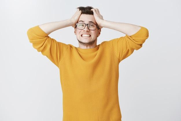 Distressed kerl in panik, der haare wirft und ängstlich aussieht