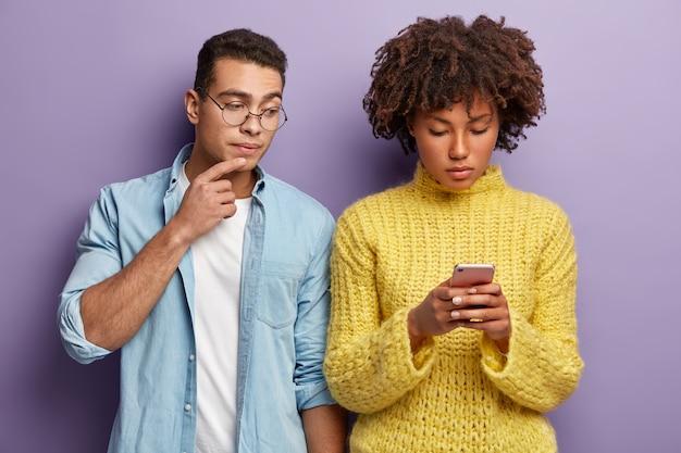 Diverse frau und mann stehen drinnen, dunkelhäutige dame im smartphone konzentriert, gibt feedback, sendet sms, neugieriger kerl späht in den bildschirm, trägt jeanshemd. multikulturelles beziehungskonzept