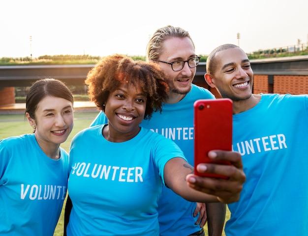 Diverse freiwillige nehmen ein selfie zusammen