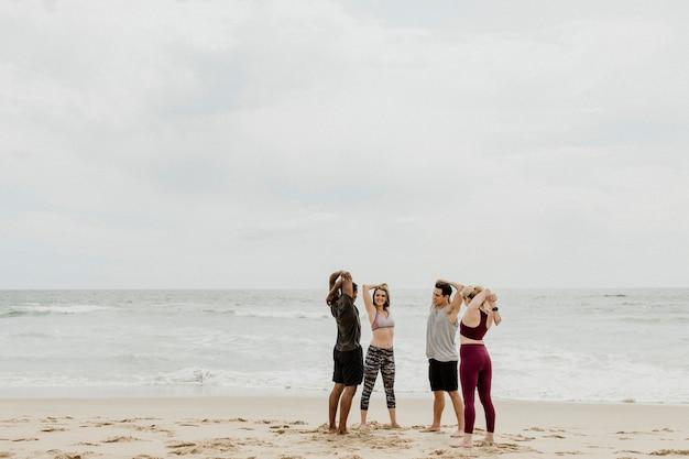 Diverse freunde dehnen sich am strand