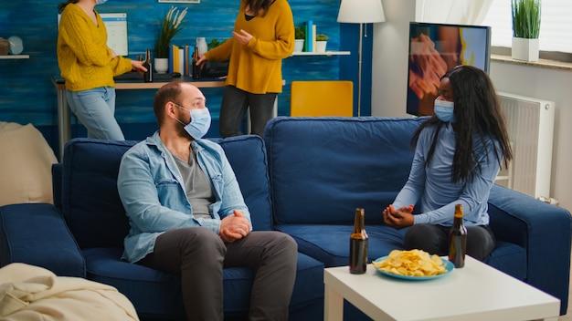 Diverse freunde diskutieren während der neuen normalen party mit schutzmaske, sozialisieren abstand halten auf dem sofa, trinken bier und essen schlangen. gruppe von multiethnischen menschen, die freizeit genießen