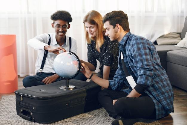 Diverse freunde gehen auf eine reise. sie planen mit dem globus. helles wohnzimmer.