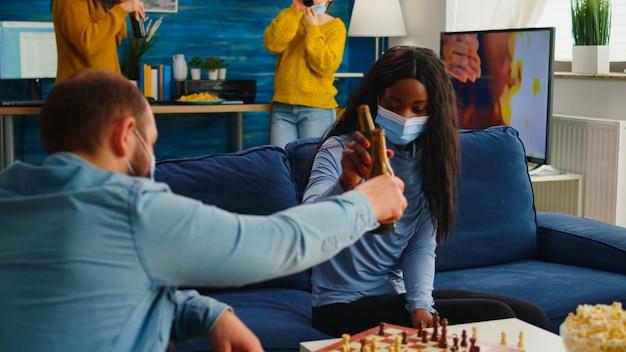 Diverse freunde klirren bierflaschen, die zu hause schach spielen und halten soziale distanz, um krankheiten mit covid19 während der globalen pandemie mit gesichtsmaske zu verhindern. gemischte leute, die brettspiele genießen
